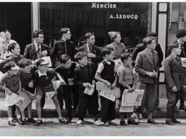 fotografie di guerra robert capa bambini con giornale in mano