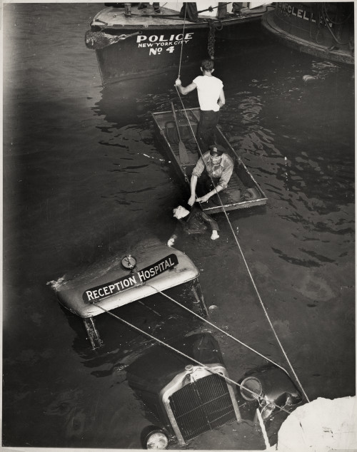 Police officer and assistant removing body of Reception Hospital ambulance driver Morris Linker from East River, New York], August 24, 1943 Gelatin silver print © Weegee/International Center of Photography International Center of Photography