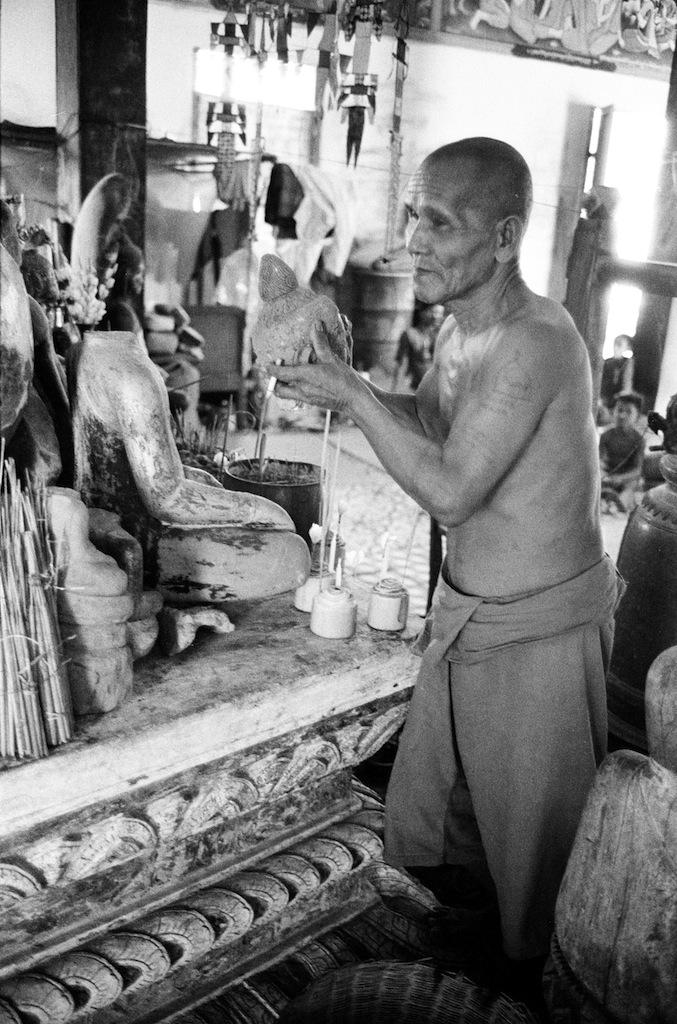 Monaco che mostra la testa tagliata di un Buddha (loc. Angkor?), 1980 © Archivio Terzani