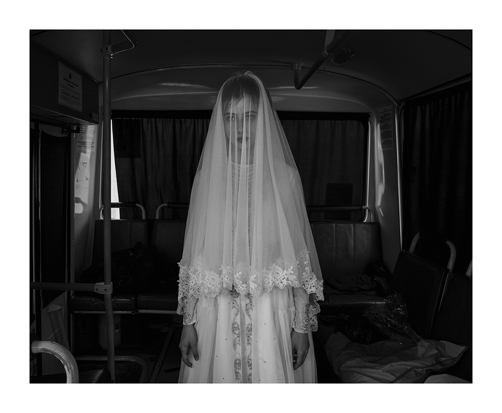 Davide Monteleone VII Photo for the Carmignac FoundationRepublic of Chechnya, Russia, 03/2013. Rada, 14 years old is trying a wedding dress designed by her sister, inside a bus during the rehearsal for the shooting of a movie on Chechen deportation. Child brides were very common in the Chechen tradition as in many other Muslim countries. Despite President Kadyrov is strongly promoting a revival of Chechen tradition and Islamic law, he was recently forced by central authority of the Russian Federation to publicly condemn the practice of child marriage, illegal in the entire Russian Federation. Shatoy.