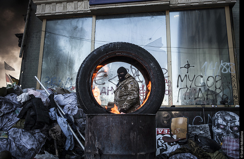 Kiev, Grushevski. Un ribelle brucia un copertone per ridurre la visuale dei tiratori scelti. © Sandro Maddalena