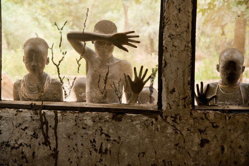 Bambini della tribù Kara che guardano attraverso le finestre, Omo Valley, Ethiopia, 2013 ©Steve McCurry