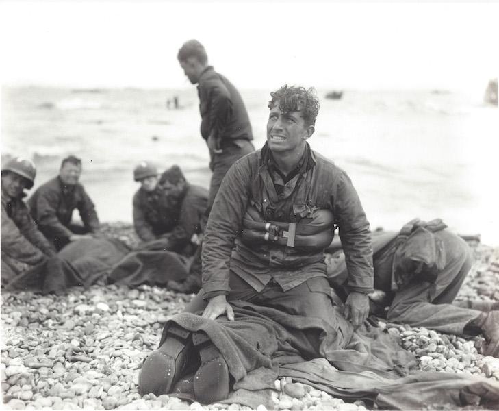 Omaha Beach Rescue. Normandia, Francia. 7 giugno 1944 (D-Day+1). Il tenente Walter Sidlowski della 5th Engineers Special Brigade, eroe di Omaha Beach Rescue, sulla spiaggia qualche minuto dopo il salvataggio di un compagno. Il soldato dietro di lui fuma una sigaretta, rivelando così che la fotografia è stata scattata quando la sèpiaggia non era sotto il fuoco nemico.  Foto di Walter Rosenblum.