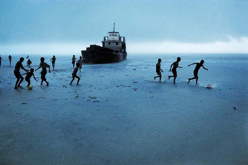 Steve McCurry, Children playing football with  Abandoned Boat, Burma, 1995.  Digital Type-C print on Fuji Crystal Paper, 40 x 60 inches Courtesy Peter Fetterman Gallery, Santa Monica, CA