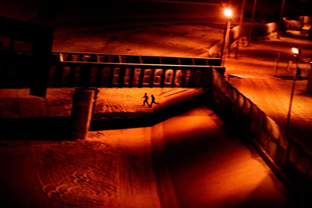 Due uomini che cercavano di entrare illegalmente negli USA corrono lungo il letto asciutto del fiume Rio Grande nei pressi di Ciudad Juárez, in Messico, dopo essere stati scoperti dalla polizia di confine statunitense. El Paso, Texas. U.S.A. 2011  © Paolo Pellegrin