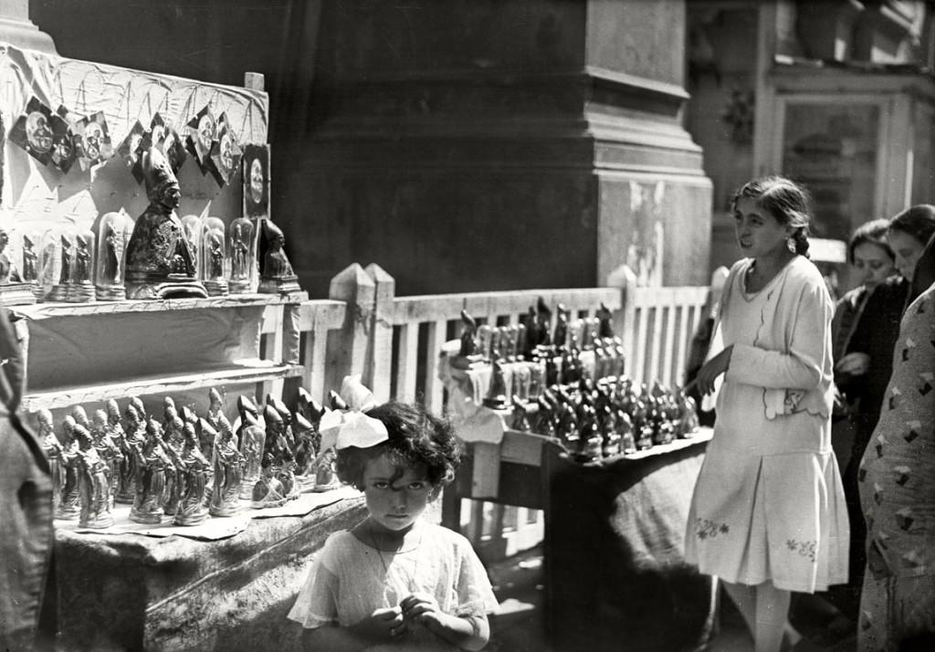 Festa di San Gennaro, bambina davanti a una bancarella con statuette del santo  Studio Troncone, anni Trenta © Stefano Fittipaldi, Archivi Parisio e Troncone, Napoli
