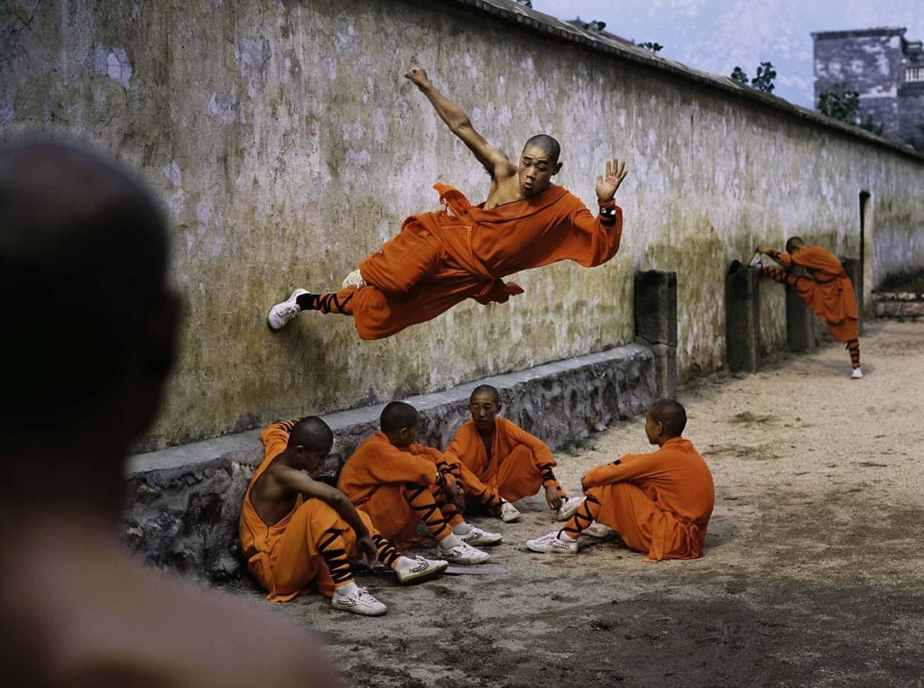Steve McCurry: A young monk runs along the wall over his peers. Hunan Province, China, 2004. ©Steve McCurry.