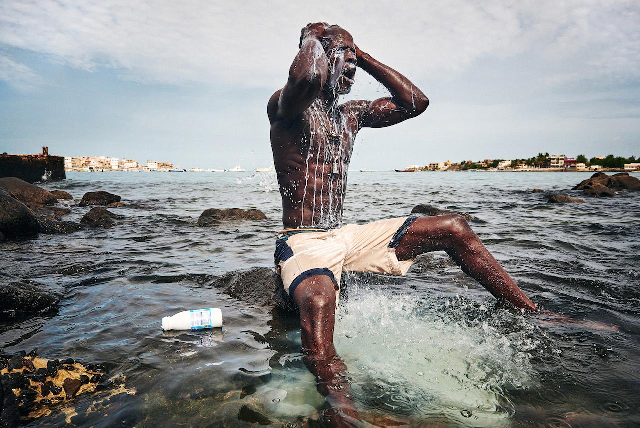Sport, Secondo premio - Foto 1 Christian Bobst, Svizzera, 2015 Gres-gris Wrestlers del Senegal Kherou, un giovane campione di wrestling, inscena un rito nell'acqua del mare versandosi latte sul corpo per ottenere l'aiuto di uno spirito che abita tra le pietre a riva. Dakar, Sierra Leone, 11 agosto 2015