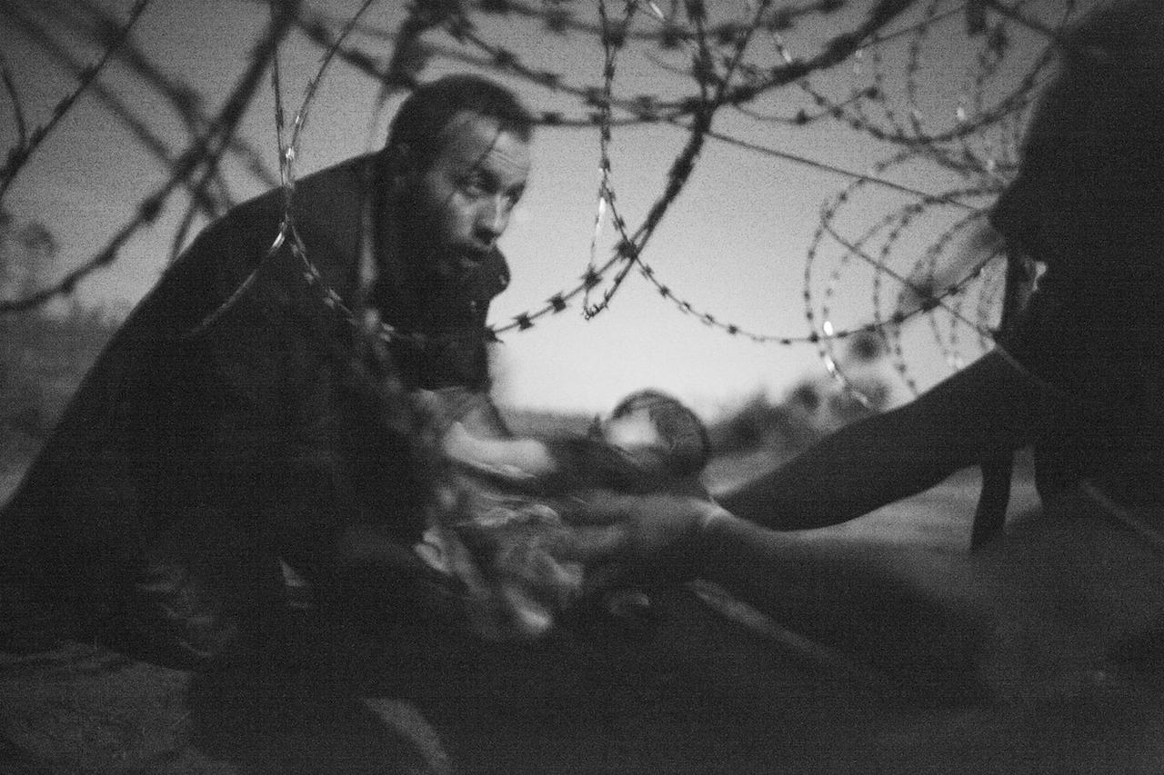 Premio World Press - Foto dell'anno Warren Richardson, Australia, 2015 Speranza per una nuova vita Un uomo aiuta a passare un neonato attraverso il filo spinato di un cancello al confine tra Serbia e Ungheria, nella città di Roskzke, in Ungheria, il 28 agosto 2015.