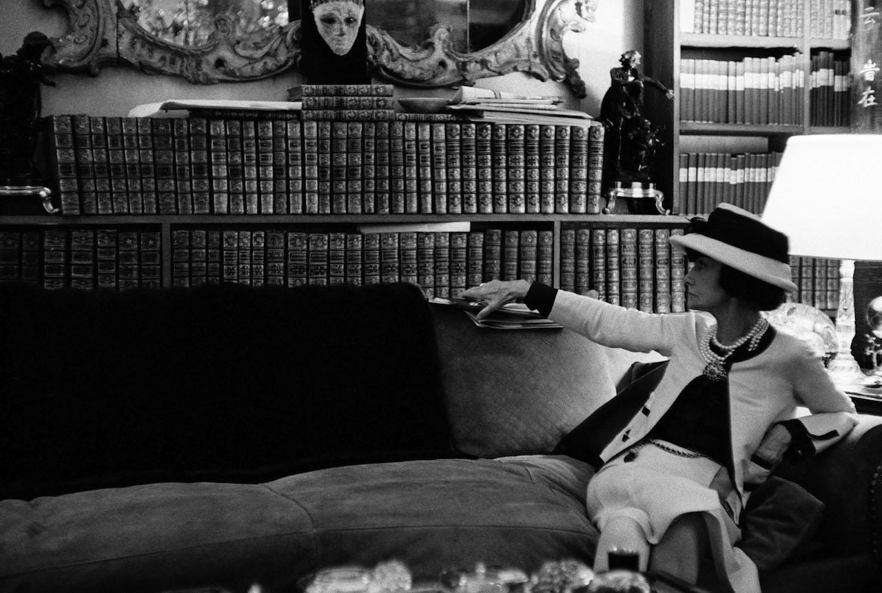 Douglas Kirkland Ritratto di Gabrielle Chanel sul suo divano, mentre guarda la sua biblioteca, luglio 1962 Fotografia Collezione Douglas Kirkland, Los Angeles © Douglas Kirkland