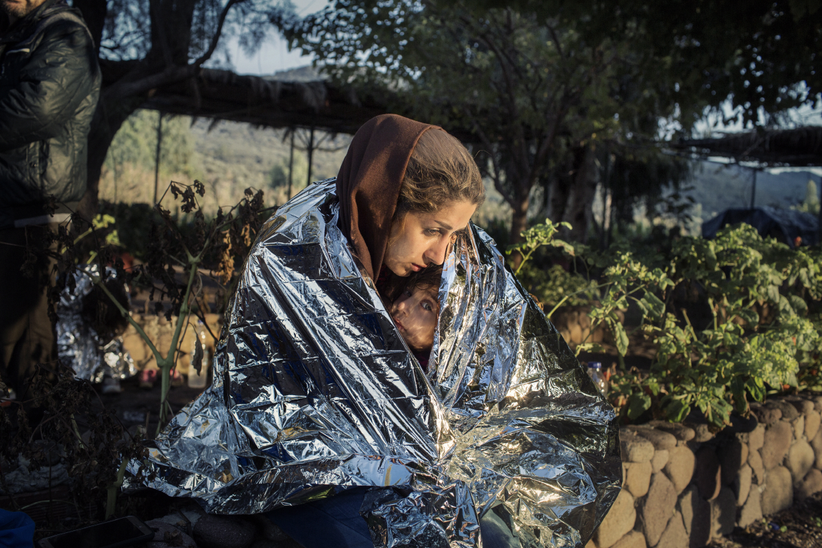 Lesbos, Greece Oct. 18, 2015. A mother and child  wrapped in an emergency blanket after disembarking on the beach of Kayia, on the north of the Greek island of Lesbos. © Alessandro Penso