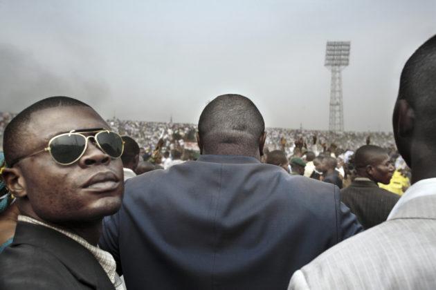 "Guy Tillim Jean-Pierre Bemba surrounded by his body guards walks into an election rally in central Kinshasa, 2006 dalla serie ""Congo Democratic"" stampa inkjet ai pigmenti su carta cotone 49,5 x 72 cm © l'artista"