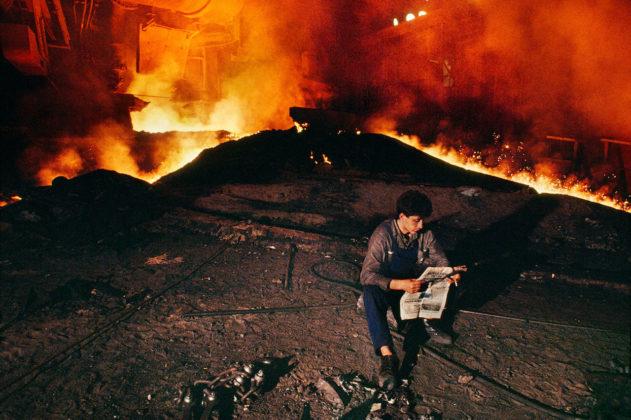 steve mccurry mostra mostra modena rgazzo che legge con incendio sullo sfondo